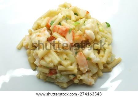 Macaroni, pasta with white cheese, shrimp, crab stick and onion - stock photo