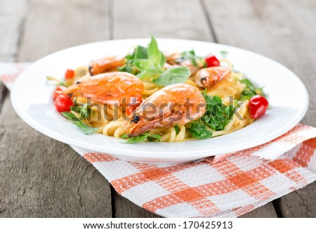 Macaroni with prawns and herbs on wooden table - stock photo