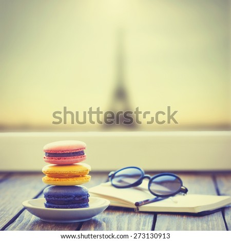 Macarons and little notebook with glasses on wooden table and Eiffel tower background - stock photo