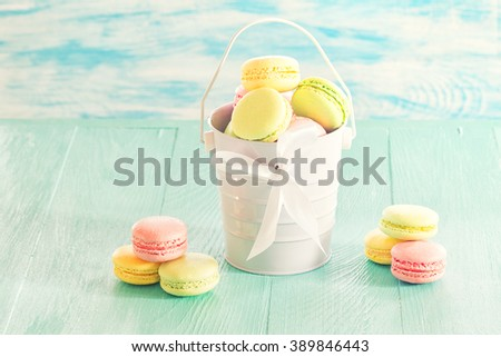 macarons in a bucket on wooden surface - stock photo