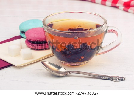 Macaroons and black tea. Refined sugar, macaroon, a Cup of strong black tea and a tea spoon on the table. Breakfast. To drink tea with sweets. Dessert, sweet tea. Good morning, - stock photo