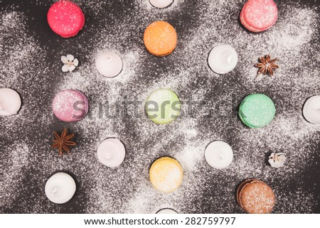 Macaroons and marshmallow on black background, anice and flowers. Sweet backgrownd - stock photo