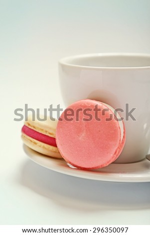 macaroons cookies and tea cup on a white background with a small depth of field (shifted the white balance) - stock photo