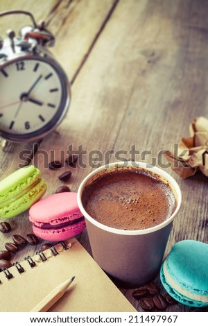 macaroons, espresso coffee cup, sketch book and alarm clock on wooden rustic table, vintage stylized photo - stock photo