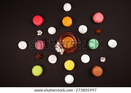 macaroons, marshmallow and coffee on black background - stock photo
