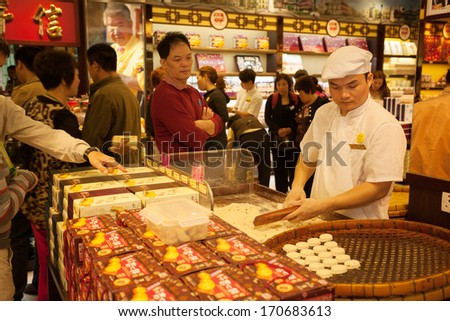 MACAU, CHINA - OCTOBER 31: Confectioner manufactures biscuits in candy store. Manufacture and sale of confectionery products is very popular business in Macau. - stock photo