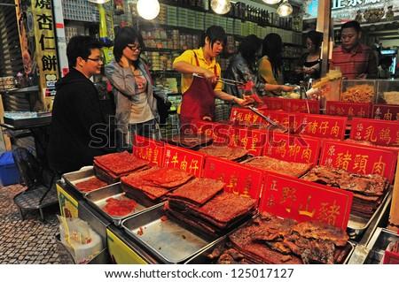 MACAU - FEB 20:Visitors buys Chines food at Macau Historic Center on February 20 2009 in Macau, China.The Historic Center of Macao was inscribed on the UNESCO World Heritage List in 2005. - stock photo