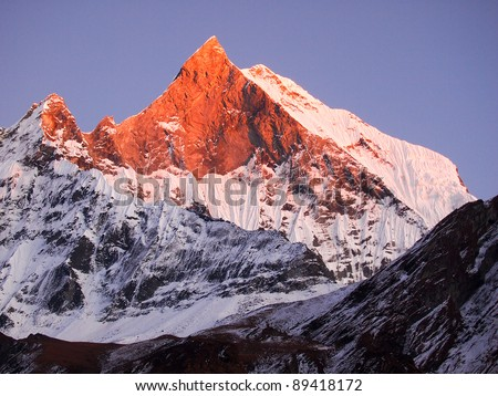 Machapuchare (Fish Tail), is a mountain in the Annapurna Himal of north central Nepal. It is revered by the local population as particularly sacred to the god Shiva. - stock photo