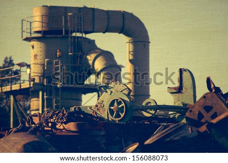 Machine behind the scrap heap works with fragmentation of the metal, aged and worn vintage style photo - stock photo