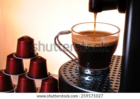 machine serving espresso coffee in a glass cup and stack of capsules - stock photo