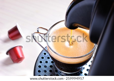 machine serving espresso coffee in a glass cup and two capsules on the table - stock photo