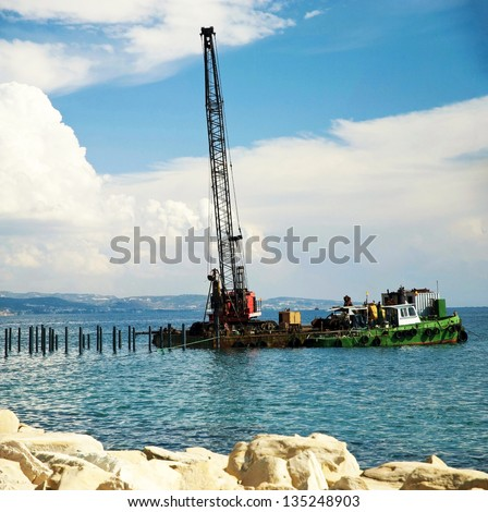 Machine used to drive piles into soil to provide foundation support for buildings or other structures - stock photo