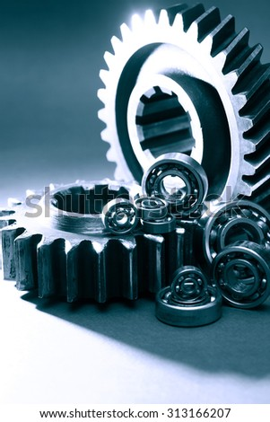 Machinery concept. Abstract composition with few ball bearings near big gears - stock photo