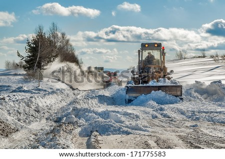 Machinery with snowplough cleaning road by removing snow from intercity highway after winter blizzard - stock photo