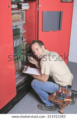 machinist worker technicians at work adjusting lift with spanners in elevator hoistway - stock photo