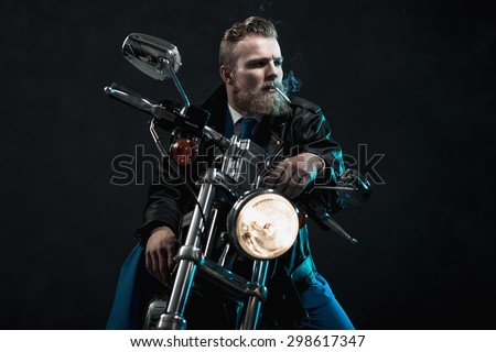 Macho businessman with a beard riding his motorbike in the darkness sitting waiting with the headlamp illuminated and a cigarette dangling from his mouth as he stares off to the right of the frame - stock photo