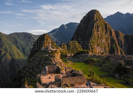 Machu Picchu at sunset when the sunlight makes everything golden-warm. Sunset at Machu Picchu, Peru. Mountain of Huayna Picchu rising above Incan ruins of Machu Picchu - Sacred Valley. - stock photo