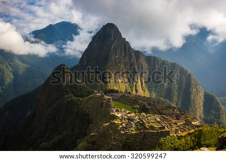 Machu Picchu illuminated by the first sunlight coming out from the opening clouds. The Inca's city is the most visited travel destination in Peru. - stock photo