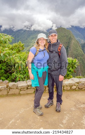 Machu Picchu, Peru - inter-ethnic couple of tourists posing for photo - stock photo