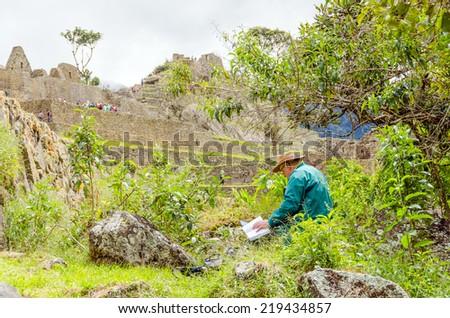 Machu Picchu, Peru - senior tourist reading in ruins - stock photo