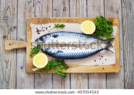 Mackarel at cutting old wooden  table with lemon and parsley - stock photo