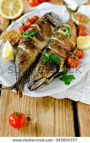 Mackerel baked with lemon, garlic and tomatoes - stock photo