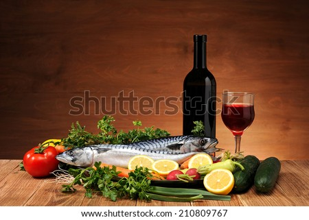 Mackerel fish, vegetables and wine on the table - stock photo