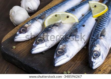 Mackerel with lemon and garlic at cutting table  - stock photo