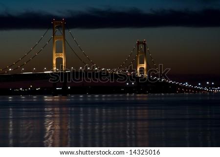 mackinaw bridge at night great colors cloudy sky - stock photo