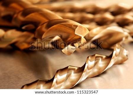 Macro abstract of titanium drill bits on workbench.  Macro with extremely shallow dof. - stock photo