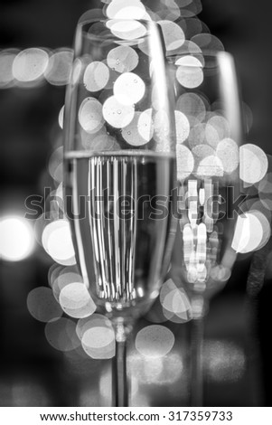 Macro black and white photo of two champagne glasses on background of Christmas lights - stock photo