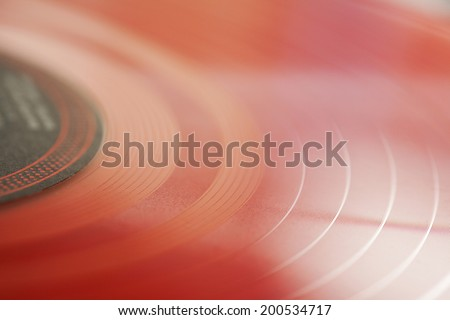 Macro close up detail view of a digital red vinyl album on a dj turntable, interior. Still life background and texture of professional musical equipment objects. - stock photo