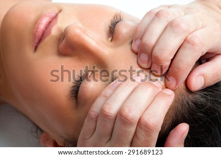 Macro close up face shot of young woman receiving massage. Therapist hand doing manipulative treatment on forehead. - stock photo
