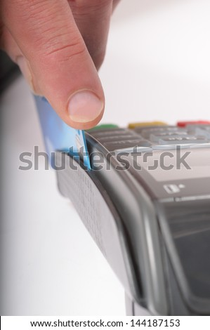 Macro / close up image of a credit card being swiped through a card machine. Focus is on the finger and front edge of the credit card - stock photo