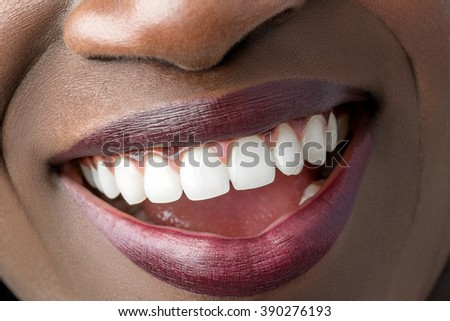 Macro close up of african female mouth showing perfect white teeth. - stock photo