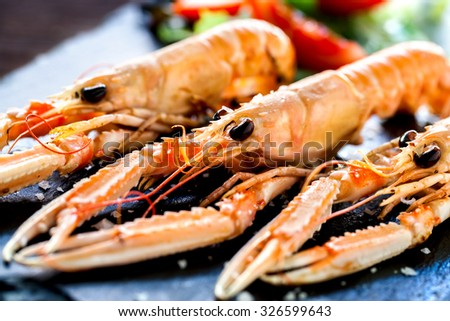 Macro close up of appetizing grilled giant craw fish platter with green salad in background.  - stock photo