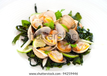 Macro close up of clam starter with lemon and greens.. - stock photo