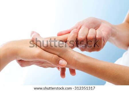 Macro close up of curative hand massage. Therapist manipulating female hand. - stock photo