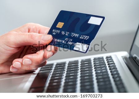 Macro close up of female hand holding credit card on laptop. - stock photo
