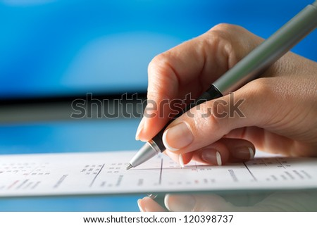 Macro close up of female hand signing document. - stock photo