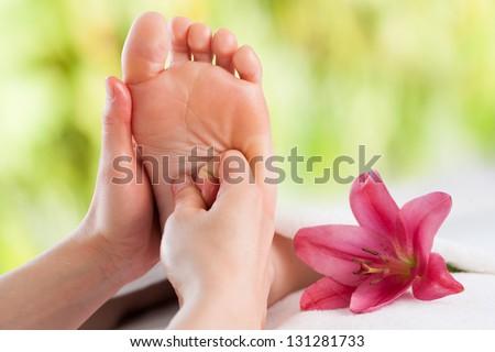 Macro close up of female hands massaging girls foot. - stock photo
