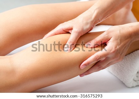 Macro close up of Hands applying pressure with fingers on calf muscle. Osteopath doing healing massage on female leg. - stock photo