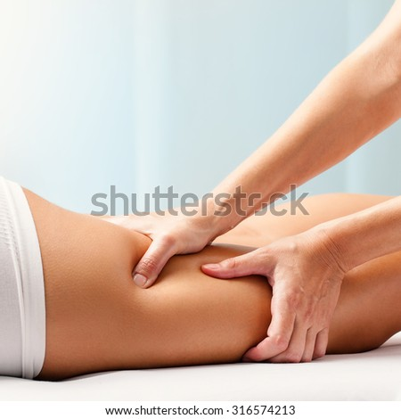 Macro close up of Osteopathic hamstring massage.Therapist applying pressure with hands on back go female leg. - stock photo