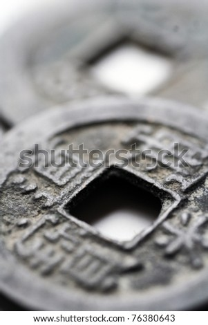 macro close-up of two ancient china coins, selective focus on closer coin - stock photo