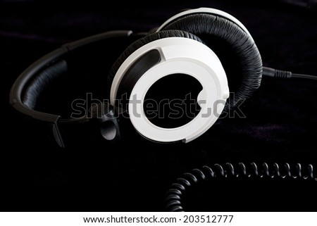Macro close up still life detail view of a pair of high end professional quality headphones isolated against a black background. Interior stereo listening equipment device. - stock photo