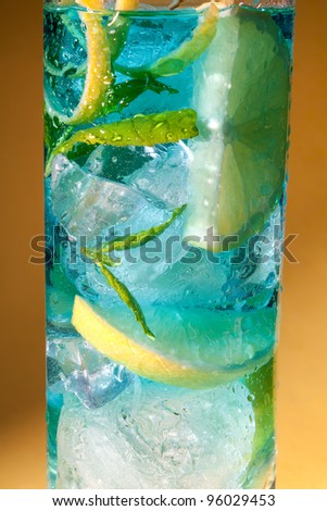 Macro closeup of a blue cocktail drink with lemon slices - stock photo