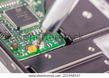 Macro closeup of a screwdriver on a hard drive circuit board depicting maintenance or repair - stock photo
