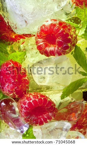 Macro closeup of a yellow cocktail drink with raspberries and mint - stock photo