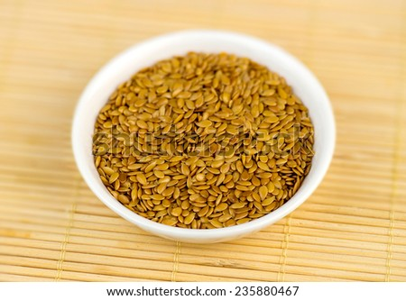 Macro closeup of flax seeds in white bowl on bamboo mat - stock photo
