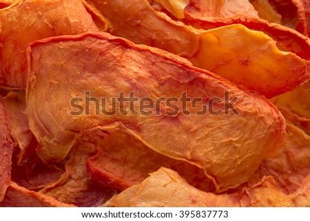 Macro closeup pile of thin sliced dehydrated orange papaya pieces - stock photo